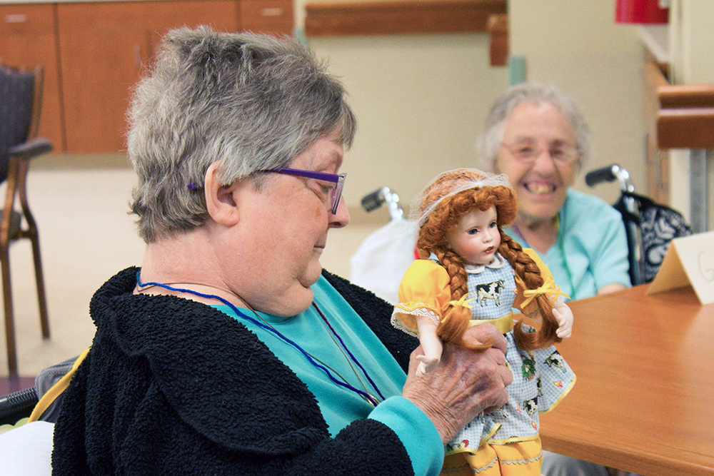 Two participants smiling as they look at one participant's doll with red braids with a yellow dress and a blue and white checkered apron with a cow on the front.