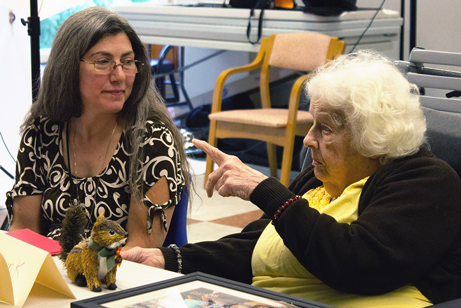 Older woman tells story about squirrel made out of straw to a middle-aged woman.