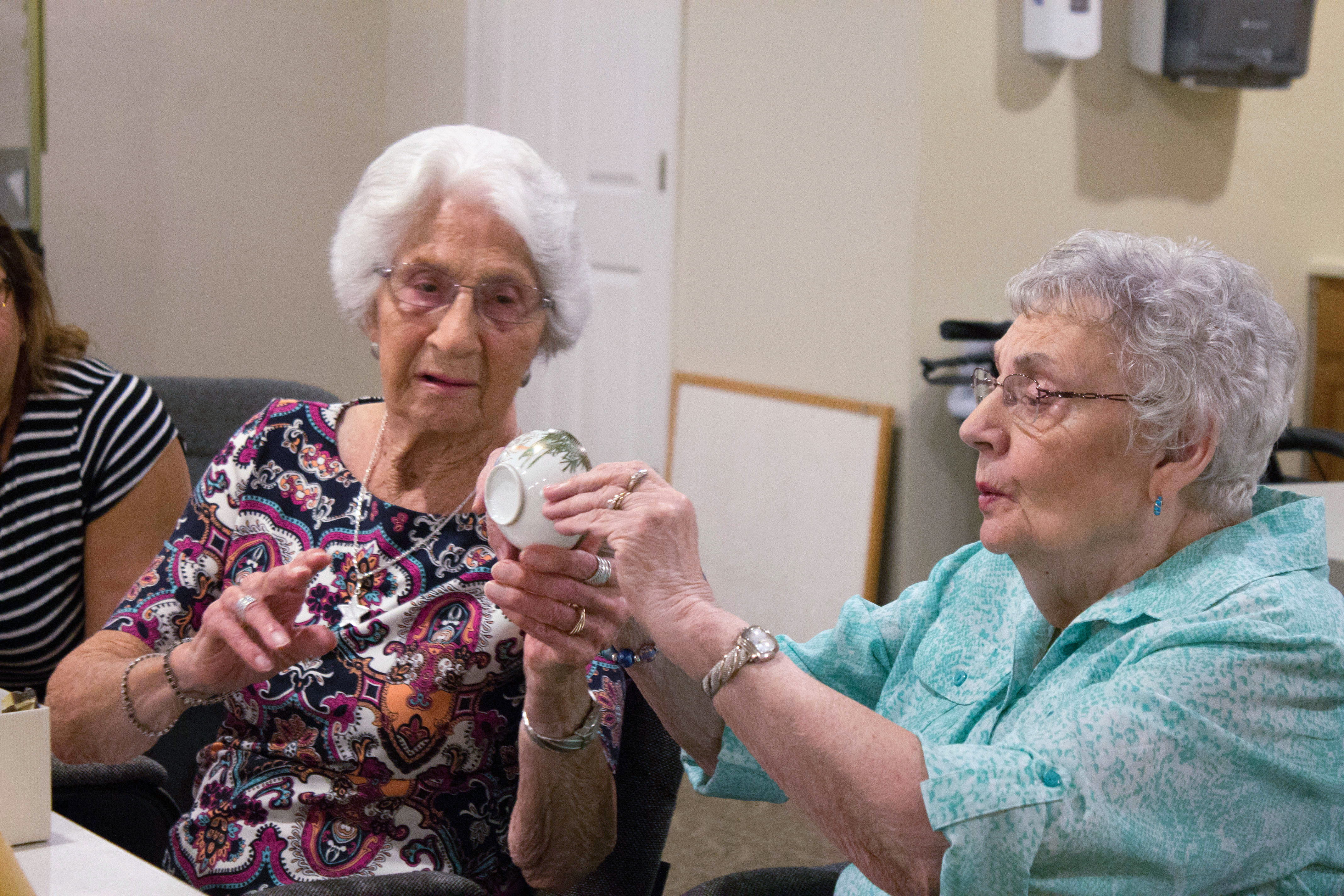 Two older women looking at a tea cup together.